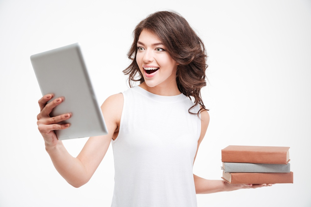 Cheerful woman choosing between tablet computer and paper books isolated on a white background.jpeg