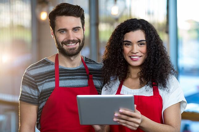 Portrait of smiling waiter and waitress using digital tablet at counter in cafe.jpeg