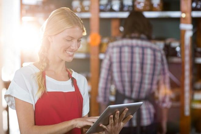 Smiling female staff using digital tablet in supermarket-1.jpeg
