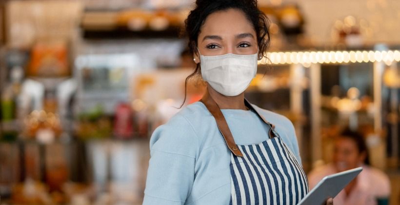 beautiful-waitress-working-at-a-restaurant-wearing-a-facemask-picture-id1225861935